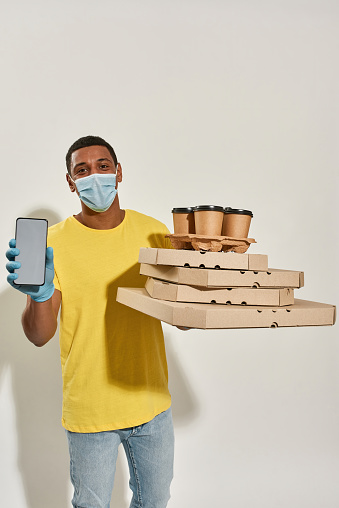 Male courier wearing protective mask and gloves looking at camera, holding smartphone mobile banking and pizza boxes and drinks isolated over gray background. Food delivery service
