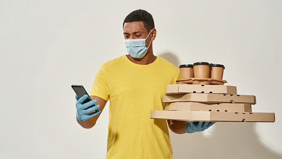 Male courier wearing protective mask and gloves using smartphone mobile banking while carrying pizza boxes and drinks isolated over gray background. Food delivery service. Web Banner