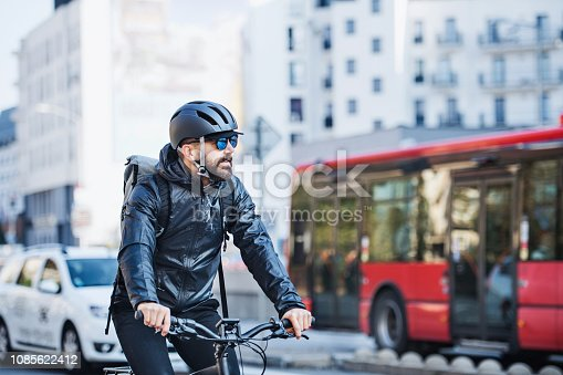 istock Male courier with bicycle delivering packages in city. Copy space. 1085622412