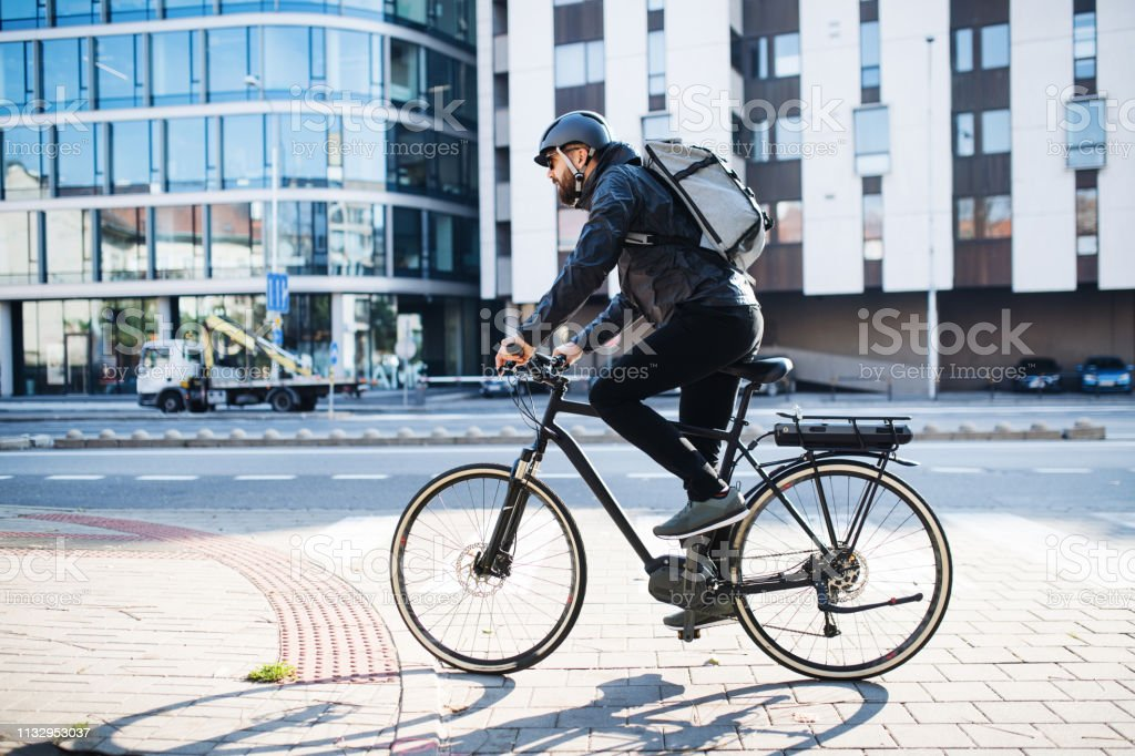 Male courier with bicycle delivering packages in city. Copy space. - Royalty-free Adulto Foto de stock