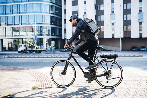 istock Male courier with bicycle delivering packages in city. Copy space. 1132953037