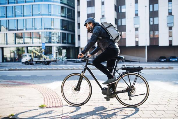 corriere maschile con pacchi di consegna biciclette in città. copiare lo spazio. - ciclismo foto e immagini stock