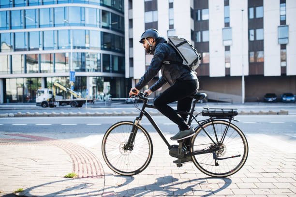 male courier with bicycle delivering packages in city. copy space. - cycling stock pictures, royalty-free photos & images