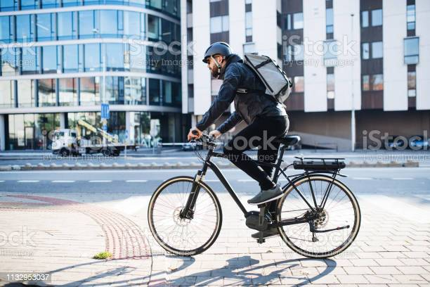Male Courier With Bicycle Delivering Packages In City Copy Space - Fotografias de stock e mais imagens de Adulto