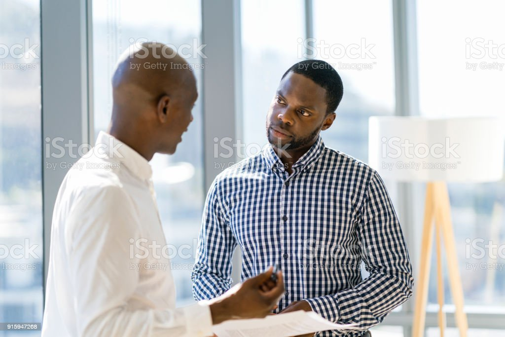 Male coworkers discussing over document at office stock photo