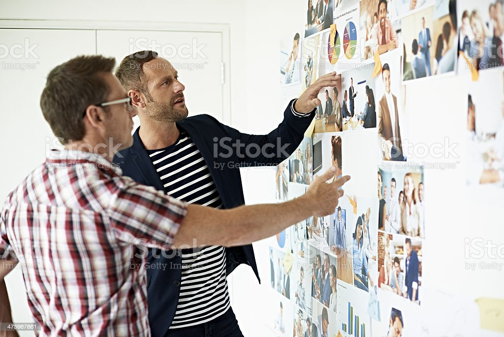 Male coworkers discussing photos Male coworkers discussing pictures hanging on the wall 40-44 Years Stock Photo