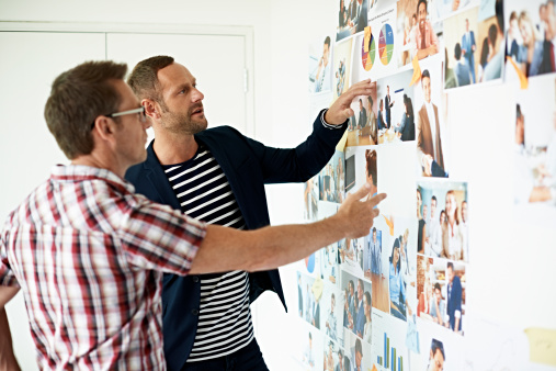 Male Coworkers Discussing Photos Stock Photo - Download Image Now