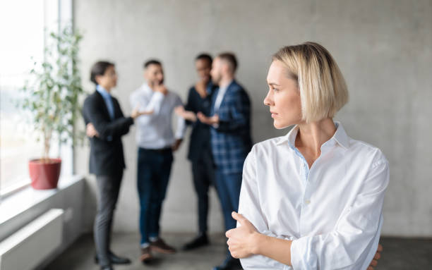 Male Coworkers Whispering Behind Back Of Unhappy Businesswoman In Office stock photo
