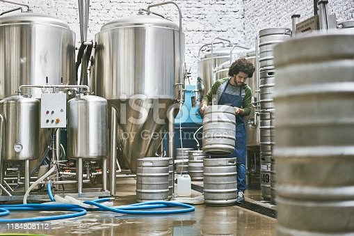 Full length view of Native American male worker stacking kegs for washing in Buenos Aires craft beer brewery.