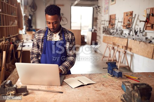 istock Male Craftsman In Carpentry Workshop For Bamboo Bicycles  Doing Accounts On Laptop 1222764950