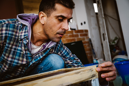 530997702 istock photo Male craftsman makes a wooden table 1129473598