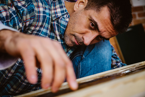 530997702 istock photo Male craftsman makes a wooden table 1129474380