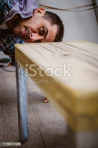 530997702istockphoto Male craftsman makes a wooden table 1129477426