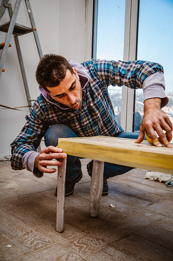 530997702 istock photo Male craftsman makes a wooden table 1129479091