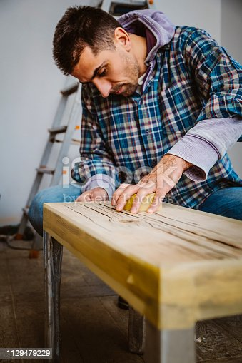 530997702istockphoto Male craftsman makes a wooden table 1129479229