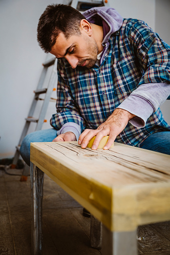 530997702 istock photo Male craftsman makes a wooden table 1129479229