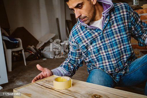530997702istockphoto Male craftsman makes a wooden table 1129481382