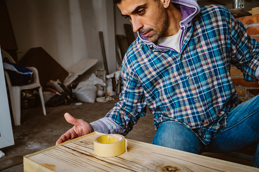 530997702 istock photo Male craftsman makes a wooden table 1129481382