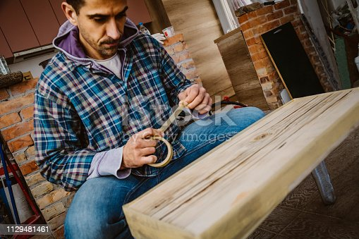 530997702istockphoto Male craftsman makes a wooden table 1129481461