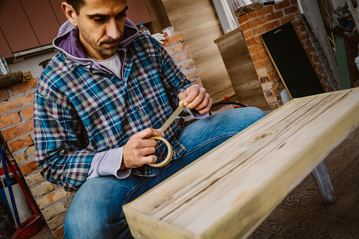 530997702 istock photo Male craftsman makes a wooden table 1129481461