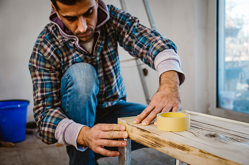 530997702 istock photo Male craftsman makes a wooden table 1129481594