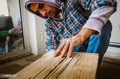 530997702istockphoto Male craftsman makes a wooden table 1129481727