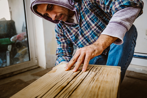 530997702 istock photo Male craftsman makes a wooden table 1129481727