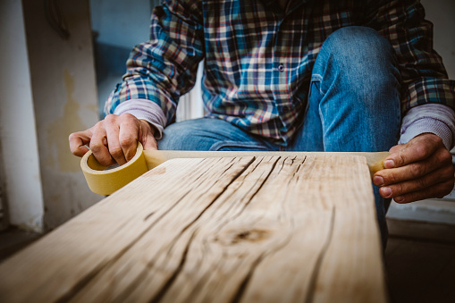 530997702 istock photo Male craftsman makes a wooden table 1129482291