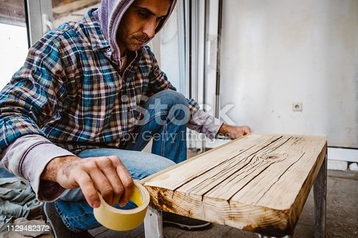 530997702istockphoto Male craftsman makes a wooden table 1129482372