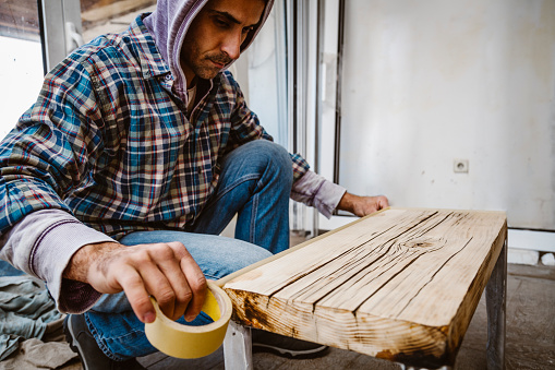 530997702 istock photo Male craftsman makes a wooden table 1129482372