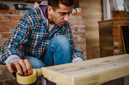 530997702 istock photo Male craftsman makes a wooden table 1129482457
