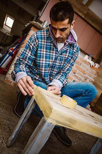 530997702 istock photo Male craftsman makes a wooden table 1129482564