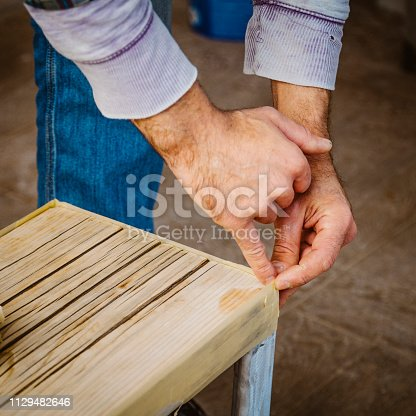530997702istockphoto Male craftsman makes a wooden table 1129482646