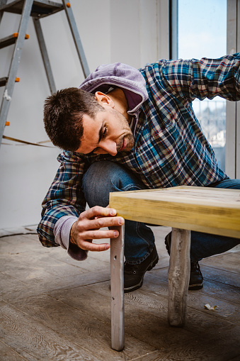 530997702 istock photo Male craftsman makes a wooden table 1129483300