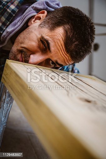 530997702istockphoto Male craftsman makes a wooden table 1129483507