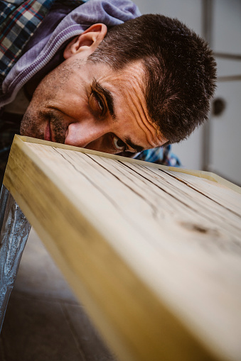 530997702 istock photo Male craftsman makes a wooden table 1129483507