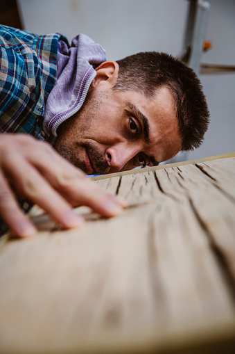 530997702 istock photo Male craftsman makes a wooden table 1129483632