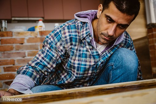 530997702istockphoto Male craftsman makes a wooden table 1129484309