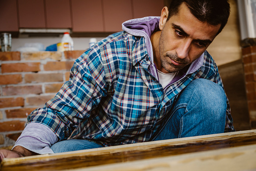 530997702 istock photo Male craftsman makes a wooden table 1129484309