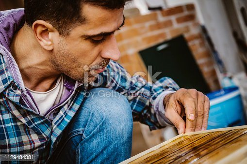 530997702istockphoto Male craftsman makes a wooden table 1129484381