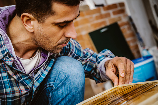 530997702 istock photo Male craftsman makes a wooden table 1129484381