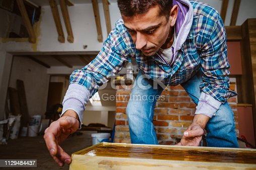 530997702istockphoto Male craftsman makes a wooden table 1129484437