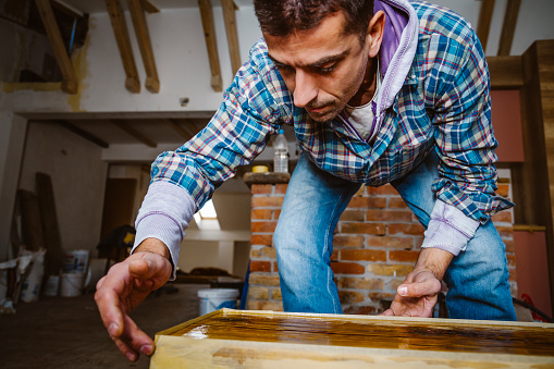 530997702 istock photo Male craftsman makes a wooden table 1129484437