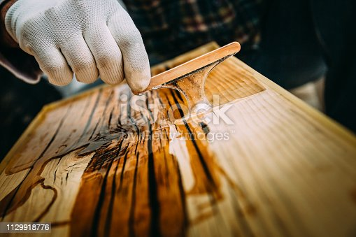 A male craftsman makes a wooden table and preparing varnishing of carpentry in his apartment which is being renovated.