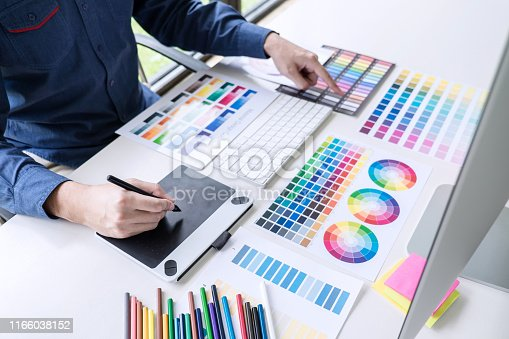 istock Male creative graphic designer working on color selection and color swatches, drawing on graphics tablet at workplace with work tools and accessories 1166038152