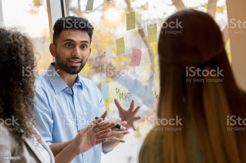 Confident young Indian male creative professional gestures as he...