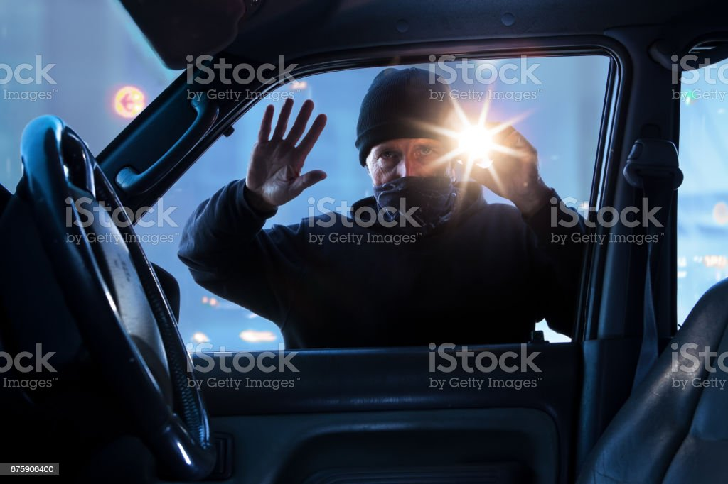 male criminal breaking into car to steal stock photo