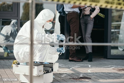 male criminologist in protective suit and latex gloves collecting evidence at crime scene