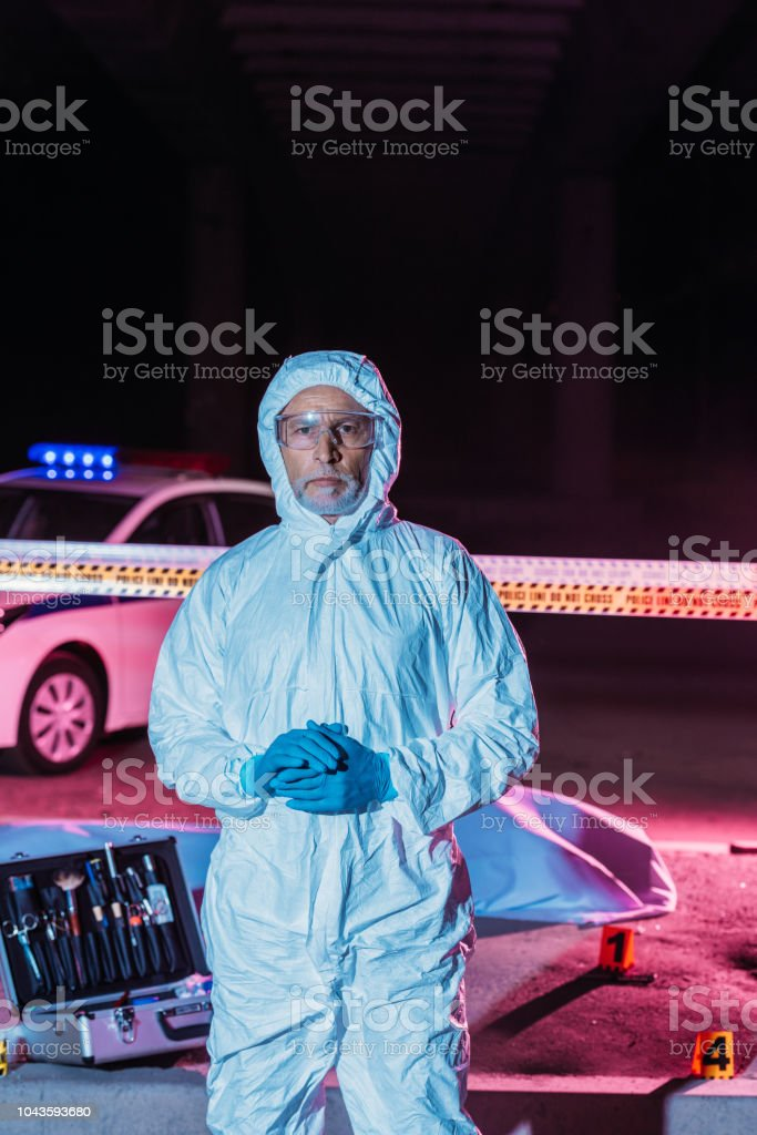 male criminologist in protective suit and mask looking at camera near crime scene with corpse in body bag and case with investigation tools stock photo