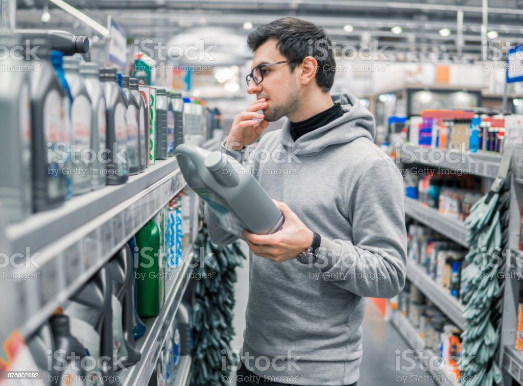 male customer buying engine lubricating oil in the car supermarket stock photo